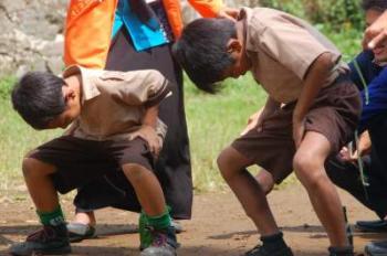 Peserta lomba berusaha memasukkan paku ke dalam botol dalam rangkaian bakti sosial Ikahimatika di Desa Sikapat, Sumbang, Banyuma.